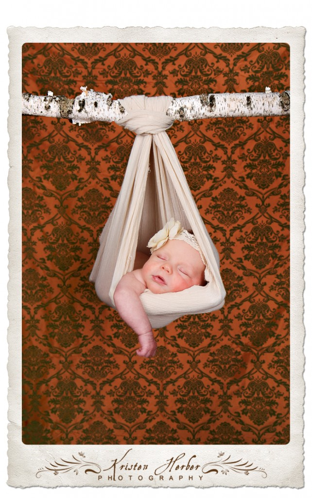newborn girl hanging from branch