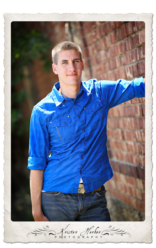 Senior Boy standing by brick wall in Blue Shirt