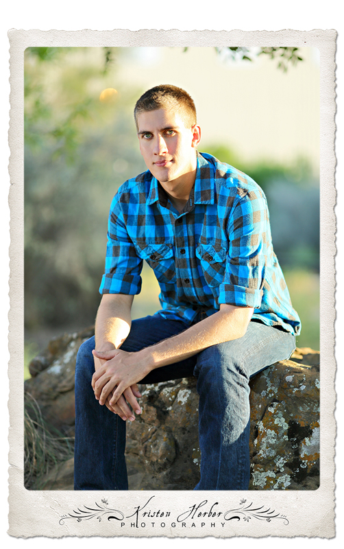 Senior Boy in blue plaid sitting outside as the sun sets