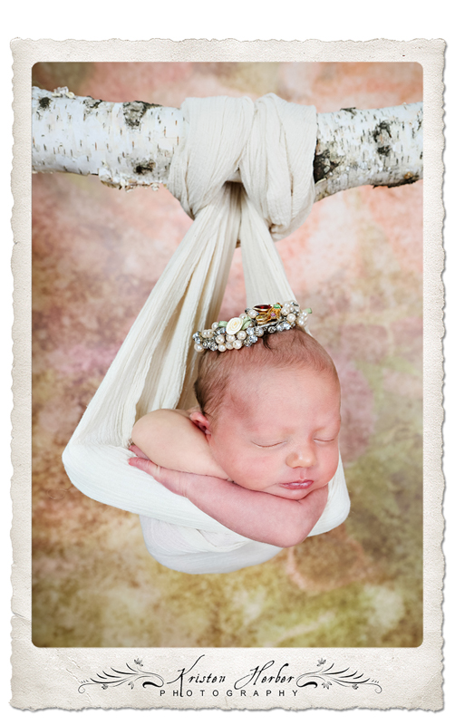 Newborn girl wearing crown swing