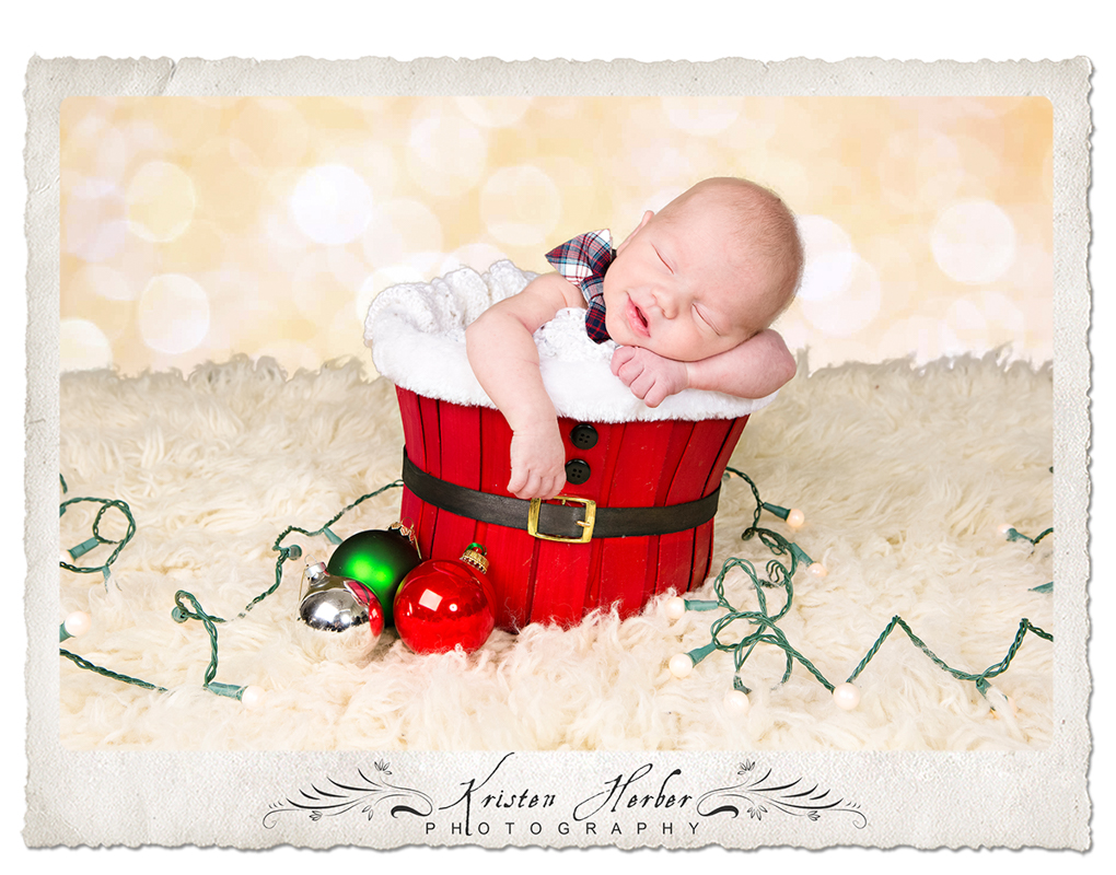 Newborn boy in red santa bucket
