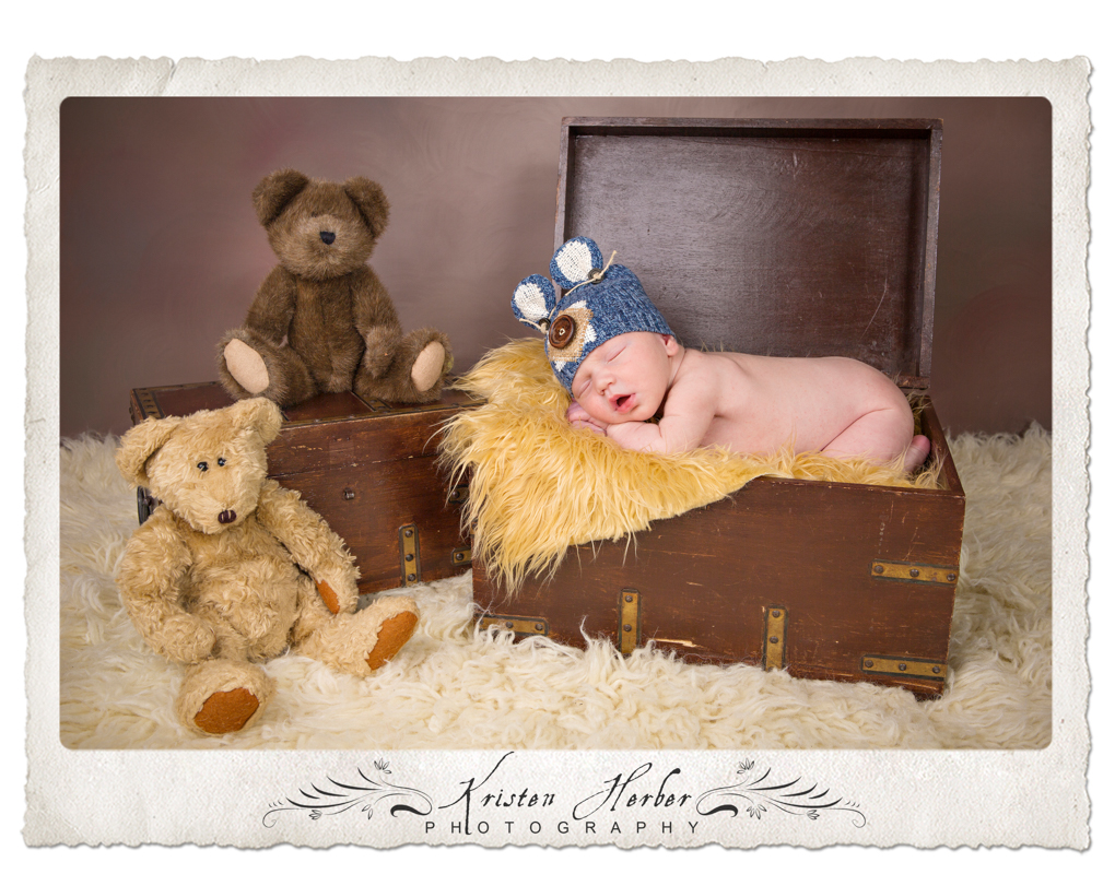 Newborn boy in wooden chest with teddy bears