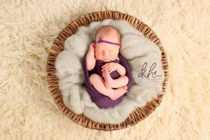 newborn wearing purple in basket