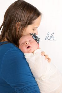 Mom holding newborn baby girl in blue