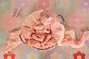 Baby girl in basket on antique quilted blanket